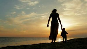 stock-footage-mother-with-baby-walking-on-sea-coast-silhouettes-sunset